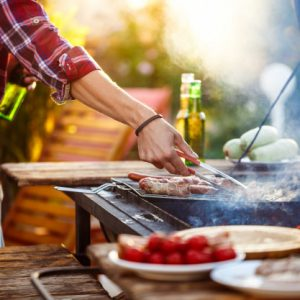 young-men-roasting-barbecue-grill-cottage-countryside_176420-1852